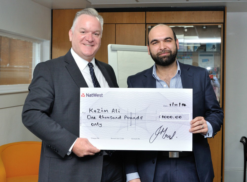 Julian Mount from Alliance Healthcare presenting a reward and recognition prize to Kazim Ali